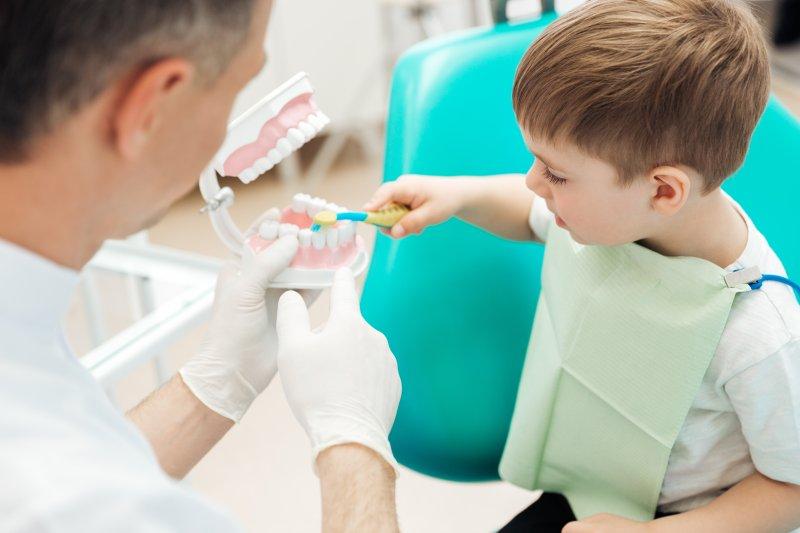 dentist teaching child how to brush