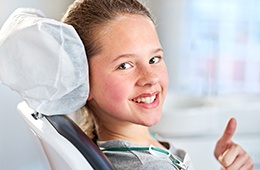 Smiling girl in dental chair giving thumbs up