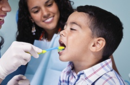 Dentist showing young boy how to brush
