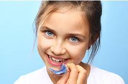 Young girl holding an oral appliance