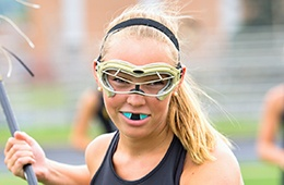 Teen girl playing lacrosse with mouthguards