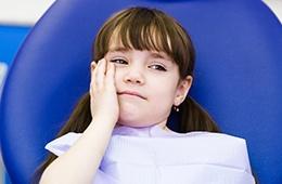 Little girl in dental chair holding cheek