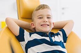 Relaxing boy in dental chair with hands behind head