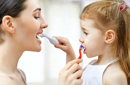 A mother and daughter brushing each other's teeth.