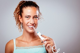 Young woman with braces using water flosser